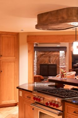 volcanic stainless fireplace surround, kitchen hood and fridge panels